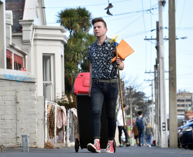 Matthew Schep, co-leader of Students for Environmental Action, helps collect rubbish in Castle St...