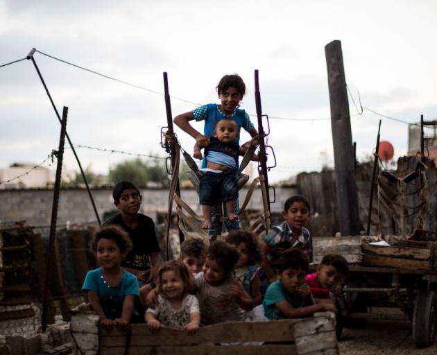 Palestinian refugee kids seen playing outside their temporary home in the northern Gaza Strip...