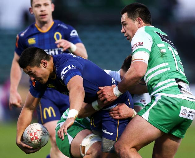 Sio Tomkinson, of Otago, is tackled by Liam Mitchell and Rob Thompson, of Manawatu, during their...