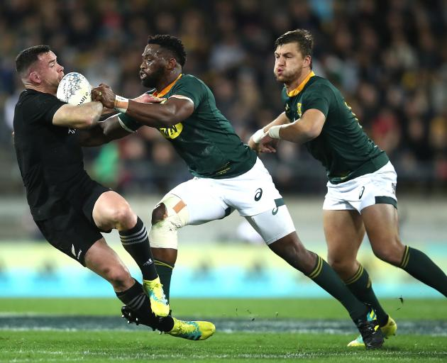 Ryan Crotty is knocked over by a brilliant South Africa defence. Photo: Getty Images