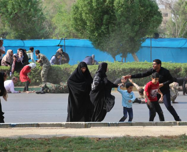 People scatter in the aftermath of a terror attack targeting a military parade in Iran. Photo:...