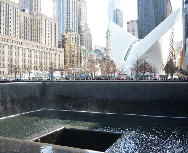 The dove-like wings of the Oculus building are pictured behind one of the two memorial pools that sit in the footprints of the former World Trade Centre Twin Towers at the 9/11 Memorial complex. Photo: Helen Speirs