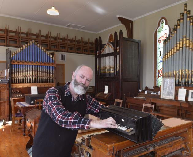 New Zealand Organ Museum Trust member Dr Ron Newton tickles the ivories of a mid-19th century reed organ built by Busson in Paris. The larger pipe organs in the background are (from left ) a Henry Jones (1882 ), George Sandford (1885) and Positive Organ C
