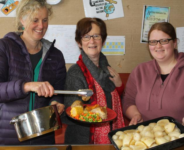The Hub free meals team (from left) Pip Gardyne, Heather Gullick and Sarah Cowan dish up a hot meal for migrant farm workers. Photo: Margaret Phillips