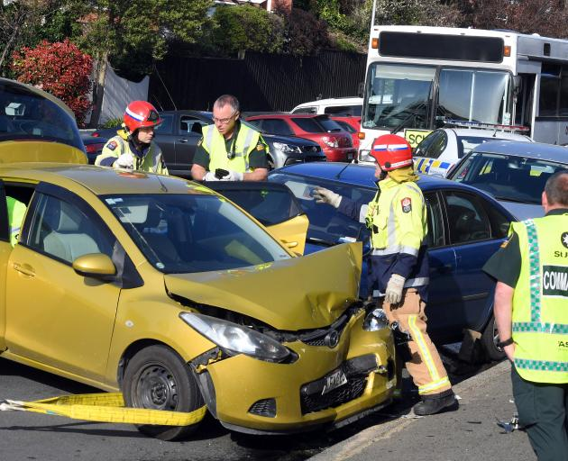 Emergency services prepare to pull a Mazda Demio out of the way so a woman (obscured) trapped between it and the Ford Focus (behind), can be removed. She was caught for more than 30 minutes before being extricated and taken to Dunedin Hospital in a modera