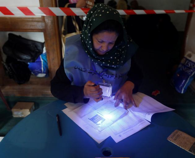 An election official checks voter's documents with an UV flashlight at a polling station during a...