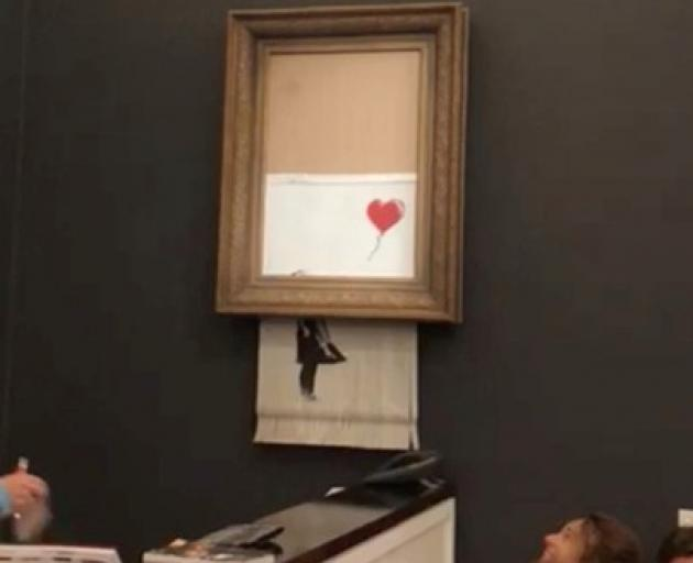 """Banksy's painting """"Girl with Red Balloon"""" is seen shredded after its sale at Sotheby auction in London. Photo: Instagram/@pierrekoukjian/@sincefineart via Reuters"""