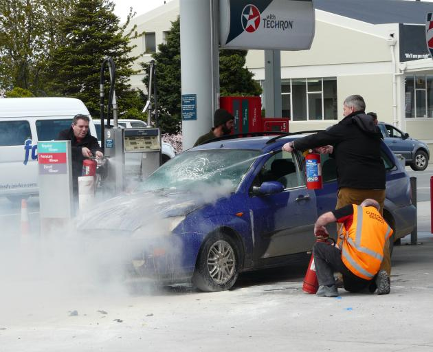 Caltex Balclutha staff and members of the public unite to control a vehicle engine fire on the petrol station's forecourt at lunchtime yesterday. Photo: Richard Davison