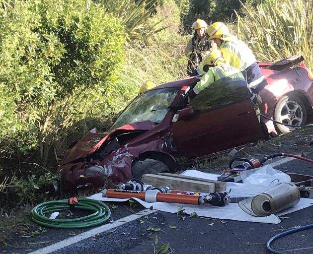 Firefighters work to extract the driver of a car following a crash at Kuri Bush, south of Brighton. Photo: Staff photographer