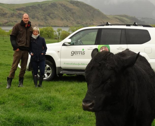 Gemma and Mike Smith and one of their Angus stud bulls on their farm overlooking Lake Hayes. Photo: Guy Williams
