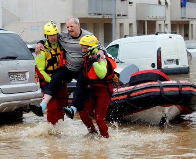 Rescue workers evacuate residents from a neighbourhood after flash floods hit the southwestern Aude district of France after several months' worth of rain fell in just a few hours overnight. Photo: Reuters