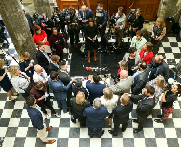 Surrounded by senior National Party MPs, party leader Simon Bridges speaks to media after a caucus meeting at Parliament yesterday. Photo: Getty Images