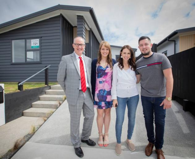 Phil Twyford and new KiwiBuild homeowners Derryn Jayne and Fletcher Ross stand with PM Jacinda...