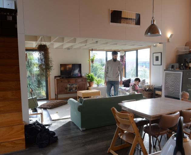 The high stud in the kitchen-dining area contrasts with the low, exposed-joist ceiling of the...