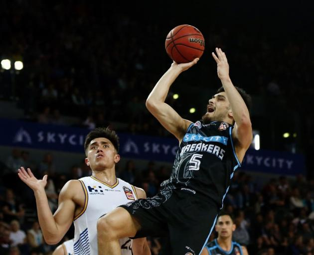 Shea Ili takes an off balanced shot for the Breakers as Bullets defender Reuben Te Rangi watches...