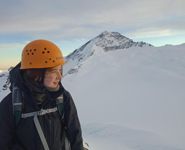 University of Otago student Maddy Whittaker on the Mt French summit, with Mt Aspiring in the background. Next month, she will walk from Bluff to the top of the South Island to raise money for Outward Bound. Photo: Supplied