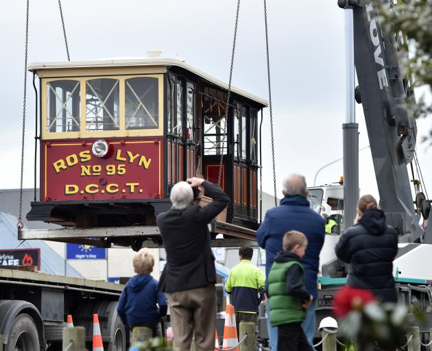 Onlookers take photographs as the Roslyn No95 cable car is lifted into the Dunedin Heritage Light Rail Trust's shed in Mornington Park. Photo: Peter McIntosh
