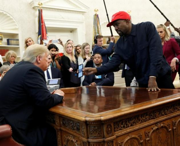 Rapper Kanye West shows President Trump his mobile phone during meeting in the Oval Office. Photo: Reuters