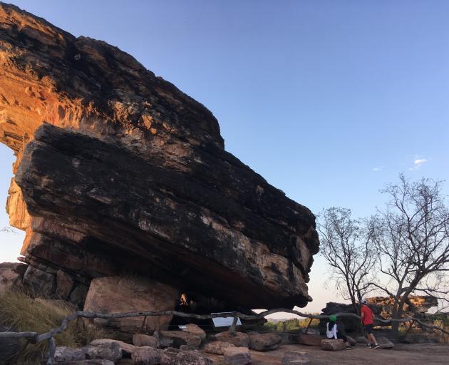 A giant rock dwarfs visitors at Ubirr. Photo: Pam Jones