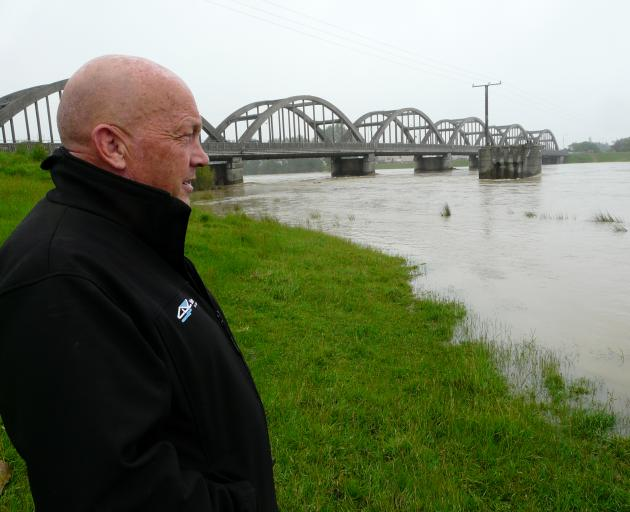 Clutha Mayor Bryan Cadogan takes stock of the Clutha River as floodwater begins to recede late yesterday. Photo: Richard Davison