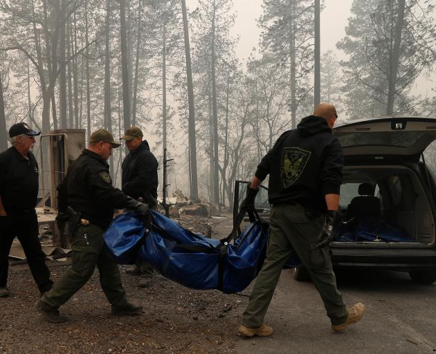 Yuba and Butte County Sheriff deputies carry a body bag with a deceased victim during the Camp...