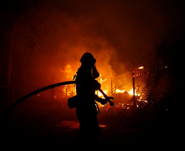 A firefighter battles the Woolsey Fire in Malibu. Photo: Reuters