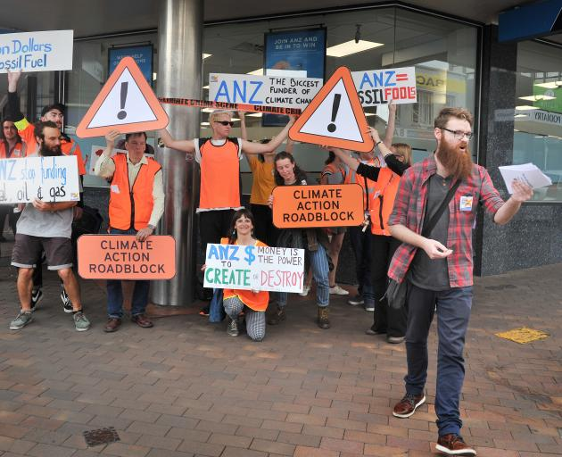 Supporters of climate activism group 350 Dunedin, who marched to an ANZ branch yesterday to deliver a recent climate change report and protest the bank's investment in the fossil fuel industry. Photo: Christine O'Connor