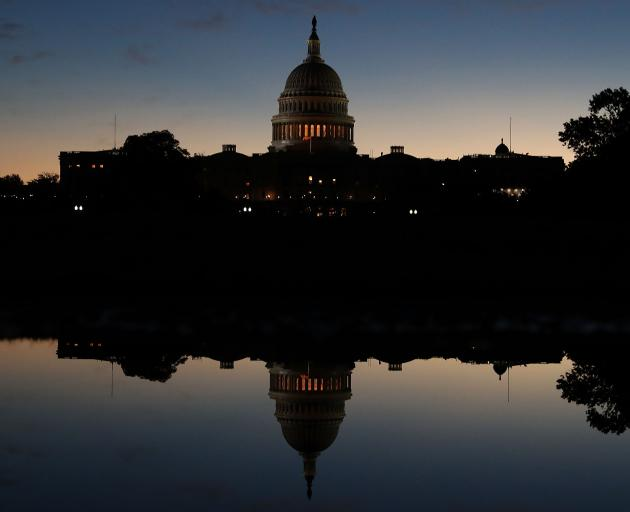 The US Capitol is reflected in a puddle of water a day after Americans voted in the midterm...