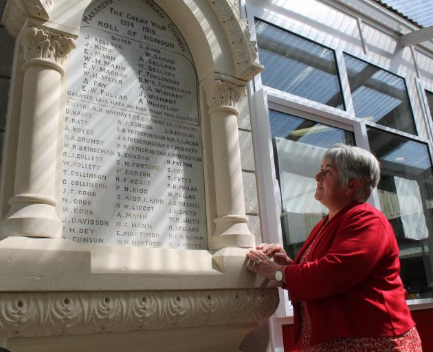 Southland researcher Ann Robbie reads the names of the former Makarewa Presbyterian Church members who served during World War 1, listed on the honour board at Makarewa School. Photo: Sharon Reece