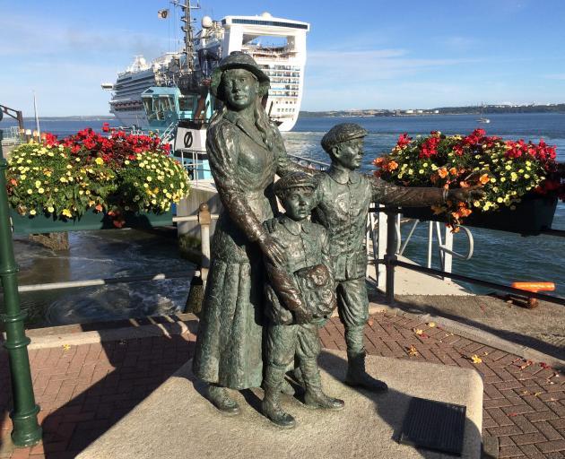 Diaspora memorial at the port of Cobh, Cork, with a modern cruise ship, Dawn Princess, leaving...