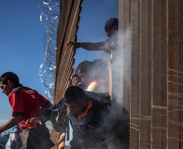 Migrants are hit by tear gas by US Customs and Border Protection after attempting to illegally cross the border wall into the US. Photo: Reuters