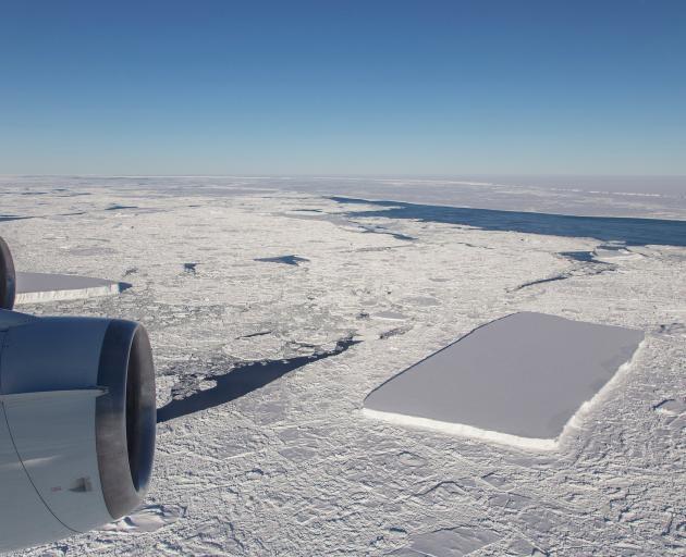 A sharp-angled, tabular iceberg floats among sea ice just off of the Larsen C ice shelf in the...