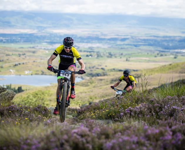 Tim Rush with Michael Vink in behind, climb Flat Top Hill, near Alexandra yesterday in the Pioneer race. Photo: Tim Bardsley-Smith