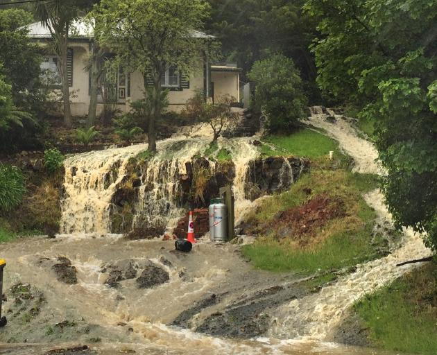 Water gushes down the hill in front of a Ravensbourne house yesterday. Photo: Gregor Richardson