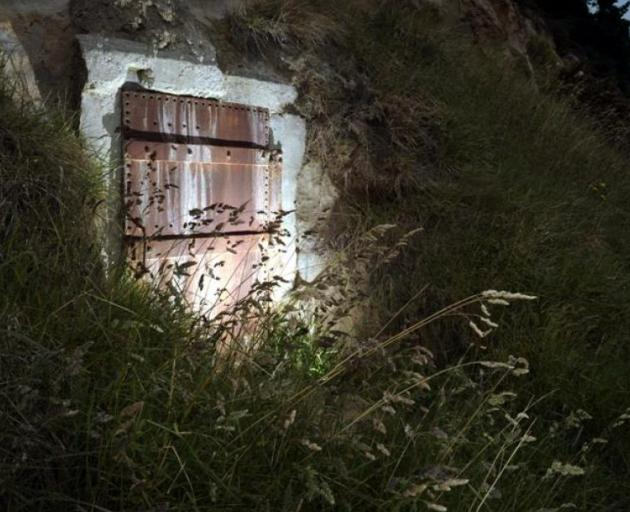 A rusted door embedded in a Dunedin cliff beside Shore St protects a short corridor leading to an...