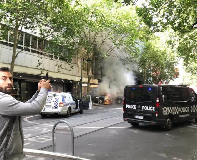 A pedestrian takes a photo of the car in flames. Photo: Twitter