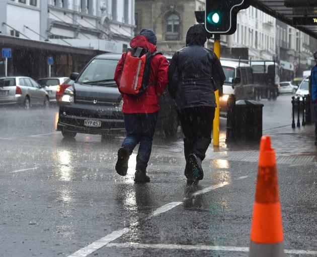Heavy rain hits Stuart St as a front moves over Dunedin yesterday.