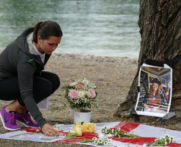 Katie Stafford places a candle at the memorial for Grace Millane in Queenstown. Photo: Mountain Scene