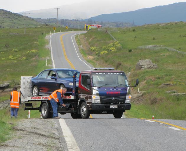 A tow truck prepares to take away a car which ran of the road this morning between Butcher's Dam...