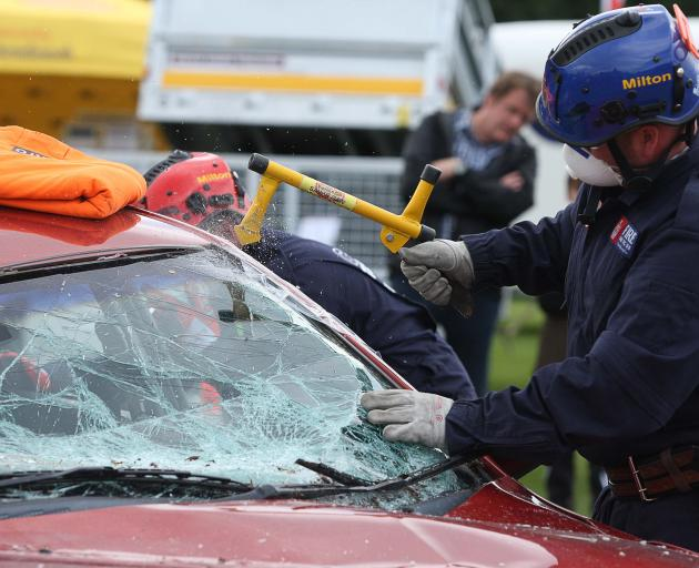 Members of the Milton crash rescue team break the windshield of a wrecked car as they...