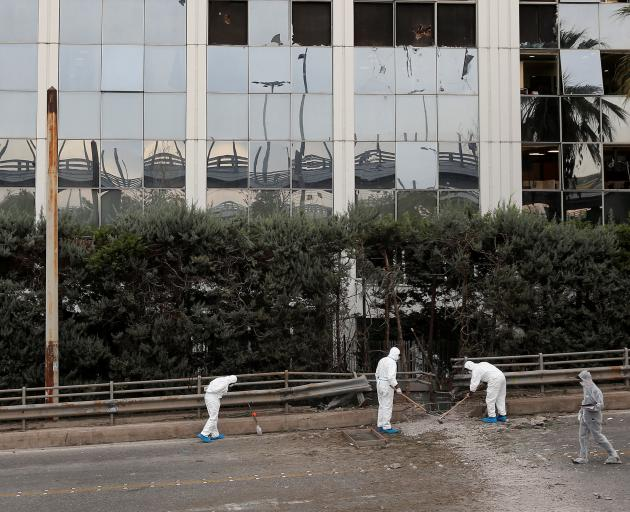 Forensic experts search for evidence after a bomb blast outside SKAI TV building in Athens. Photo: Reuters