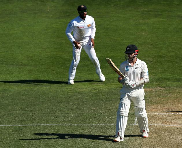 Kane Williamson looks at his bat after being dismissed 9 short of what would have been his 20th...