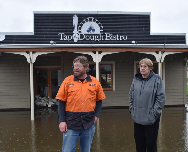 Owners Richard and Norma Emerson outside their flooded business at Middlemarch in November. Photo: Peter McIntosh