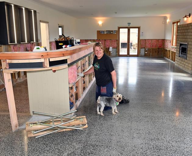 Tap & Dough Bistro co-owner Norma Emerson starts putting her restaurant back together, accompanied by Asterix the dog, after it was severely damaged in the November floods. Photo: Linda Robertson