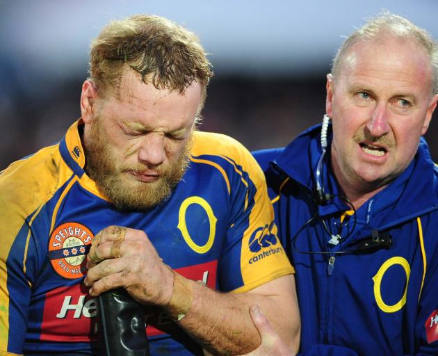 Eben Joubert, with baggage man Neville Ives is helped off the field with a dislocated shoulder in...