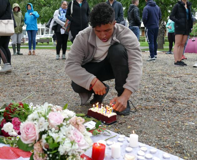 Josh Lewis, a close family friend of Grace Millane's, lights a birthday cake in her honour at last night's Queenstown vigil. Photo: Daisy Hudson