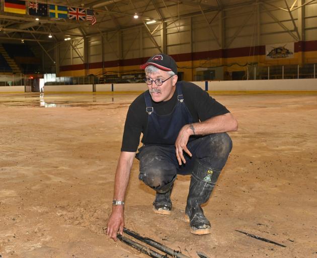 Reece Aiken, the Dunedin Ice Stadium icemaker, examines the icy surface of the stadium yesterday...