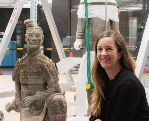 Te Papa curator Dr Rebecca Rice takes a look at one of the terracotta warriors being installed in an exhibition at Te Papa. Photo: Supplied