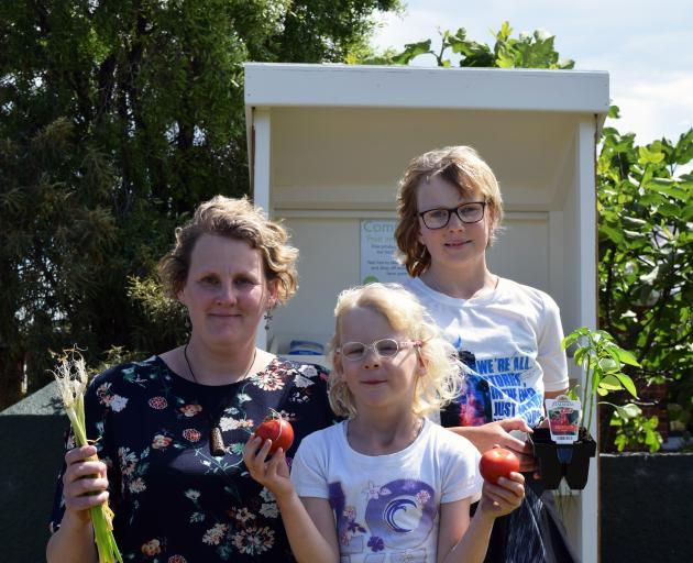 Displaying some of the produce in a community fruit and vegetable stand in Waldronville on Monday are (from left) Saddle Hill Community Board deputy chairwoman Leanne Stenhouse and her daughters Mia (6) and Amy Smith (11). Photo: Shawn McAvinue