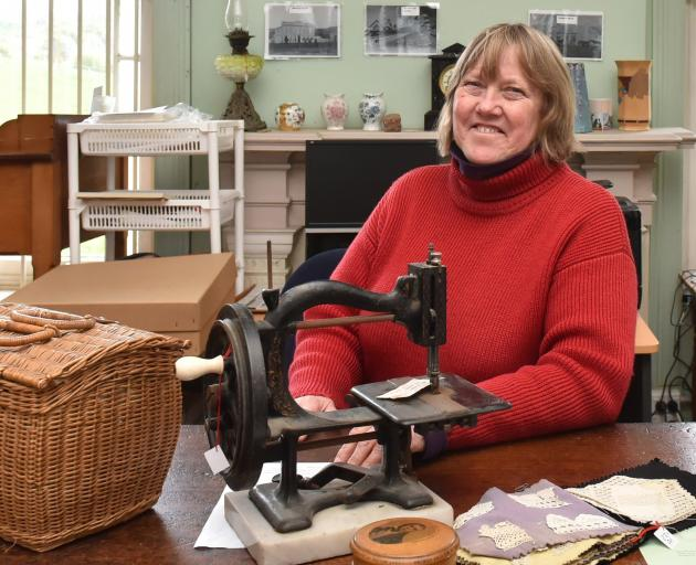 Museum curator Kay Lang with an 1870s sewing machine and equipment. Photo: Gregor Richardson